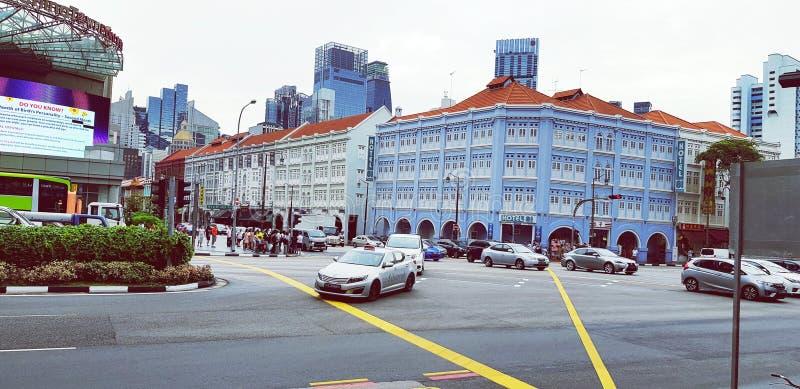 Автомобили людей ждать останавливают для того чтобы пересечь улицу в городе с старой голубой предпосылкой стиля здания на Чайна-т стоковые фото