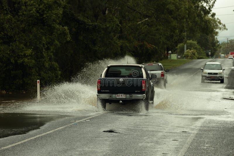 автомобили пересекая затопленную дорогу стоковое фото rf