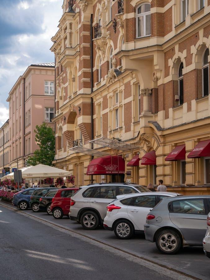 Автомобили припарковали перед классическим зданием летом стоковая фотография rf