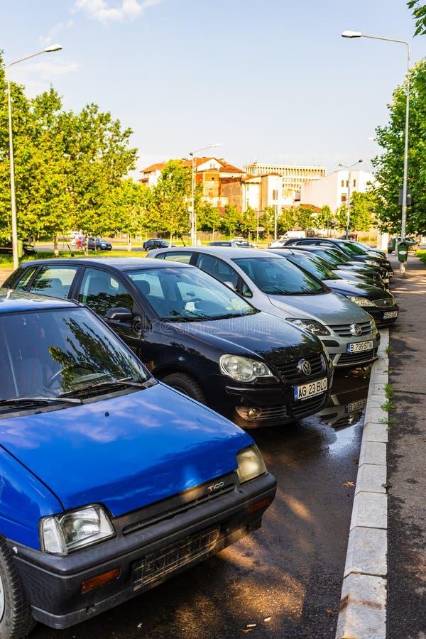 Автомобили припаркованные вдоль улицы стоковое фото