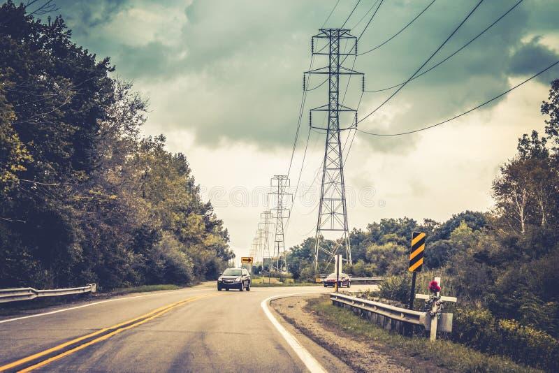 Автомобили путешествуя на дороге вокруг угла с крестом на переднем плане мрачное напоминание, который нужно управлять безопасно стоковая фотография rf