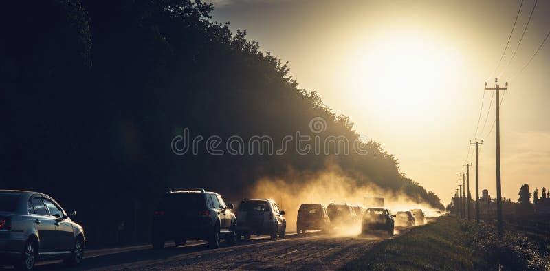 Автомобили управляют в заход солнца при пыль поднимая на дорогу сельской местности, панорамное фото стоковая фотография rf