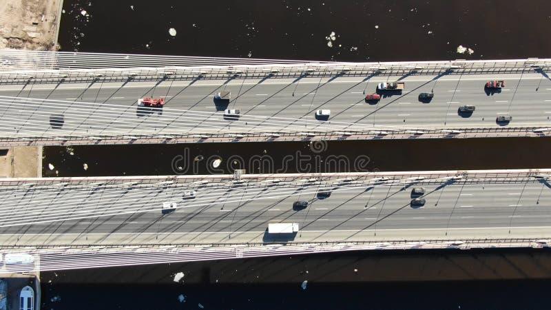 Автомобили управляют на, который кабел-остали мосте над рекой, виде с воздуха, движении камеры стоковые фотографии rf