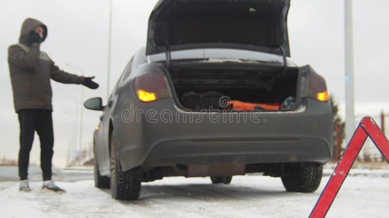 Автомобильная катастрофа Молодой человек готовя сломленный автомобиль Улавливать автомобиль для помощи Аварийный знак стоковые изображения
