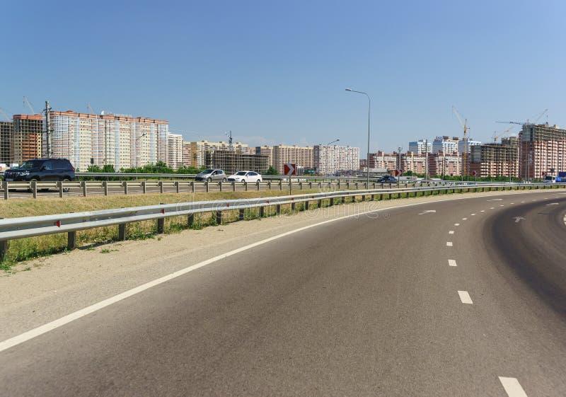 Автомобильное движение к улице названной после Питер Metalnikov Активная конструкция нового современного района в городе стоковые изображения rf