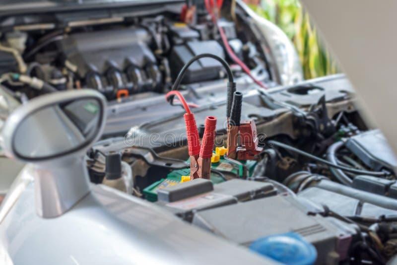 автомобильный аккумулятор зажатый с черным и красным соединительным кабелем для того чтобы перезарядить стоковая фотография rf