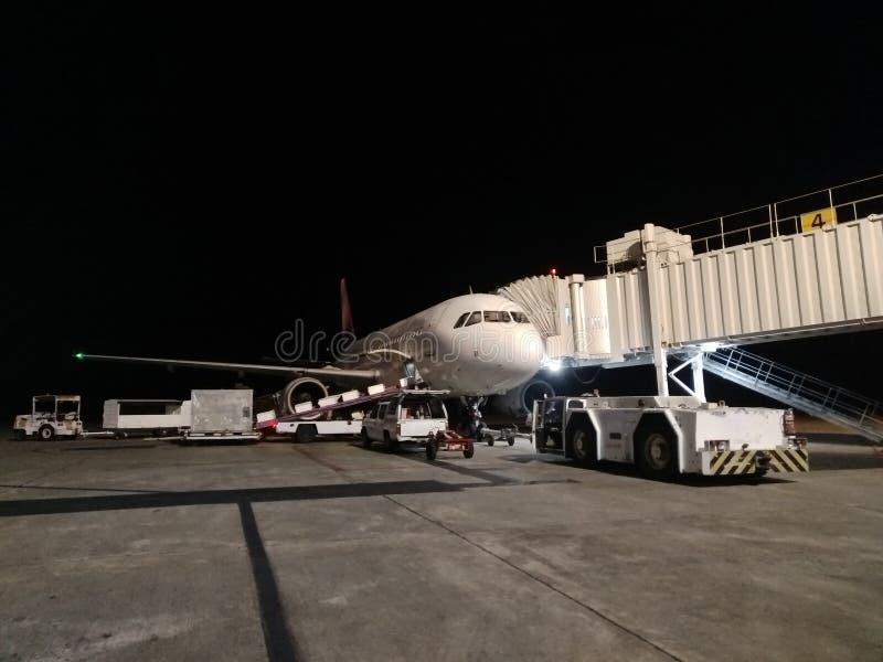 Автомобиль аэропорта, перевозящий груз в самолет ночью Услуги по доставке багажа в ночное время стоковые изображения