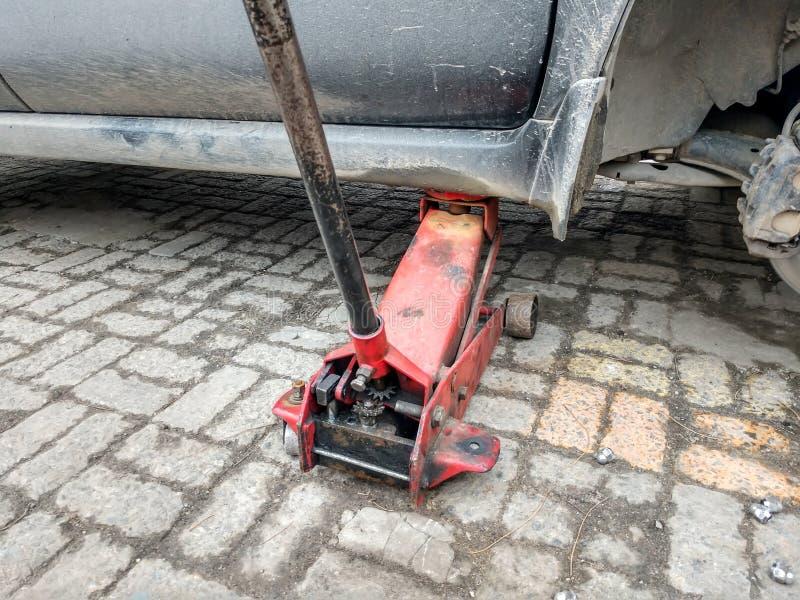 Автомобиль без колеса поднятого на красный цвет поднимает домкратом стоковое фото rf