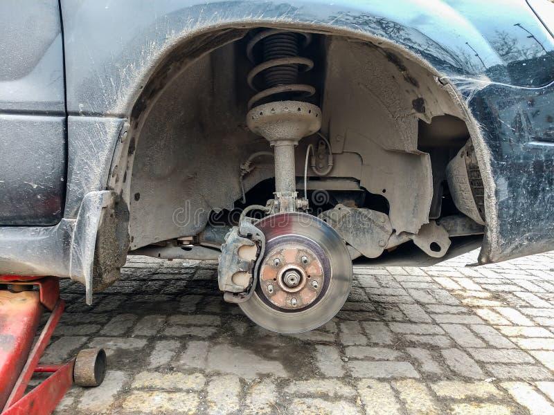 Автомобиль без колеса поднятого на поднимает домкратом Замена колеса на пункте обслуживания автошины стоковые изображения rf