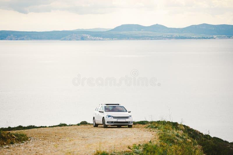 Автомобиль белого цвета, фура станции путешествует вдоль грязной улицы, каменистых дорог вдоль береговой линии в горах около побе стоковое фото