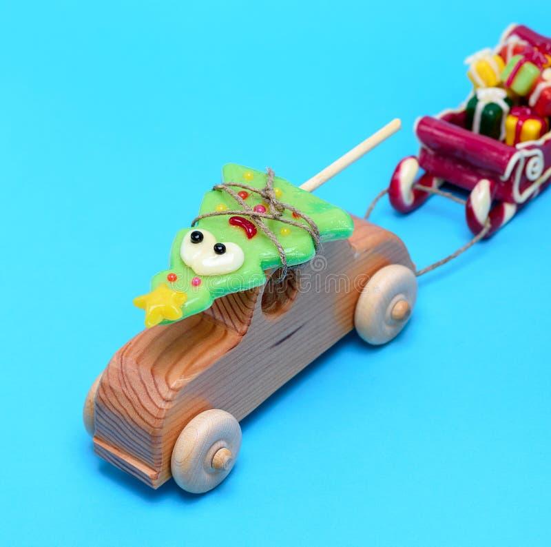Автомобиль деревянных детей носит спрус праздника карамельки и вытягивает сани с подарками стоковое фото