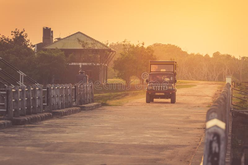 Автомобиль для сафари на заходе солнца приводы за домами на дороге стоковое фото