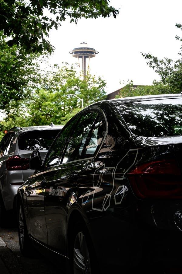 Автомобиль доли езды ReachNow с иглой космоса Сиэтл в предпосылке стоковое фото