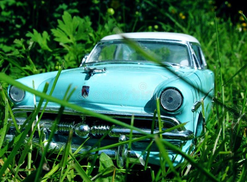 Автомобиль мяты классики зеленый в высокой траве перед встречей автомобиля стоковые изображения