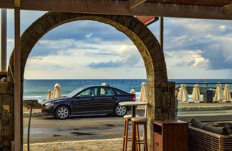 Автомобиль на предпосылке, кафе и харчевне seascape на пляже, Крите, Греции Концепция назначений перемещения Воссоздание и путеше стоковое фото