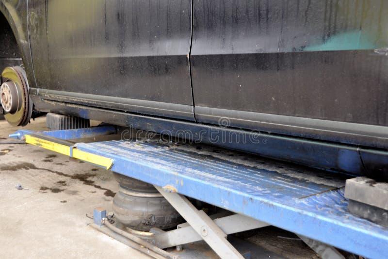 Автомобиль поднятый пневматическим поднимает домкратом, катит замену стоковое изображение rf