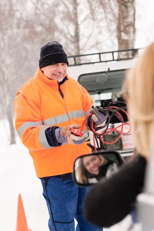 Автомобиль помощи человека сломанный женщиной начиная кабели стоковые изображения