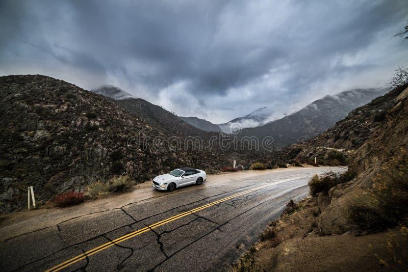 Автомобиль припарковал на кривой дороги сценарной горы влажной на ненастном пасмурном дне Концепция поездки стоковая фотография