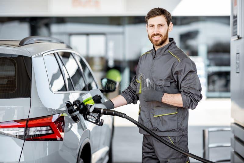 Автомобиль работника бензоколонки дозаправляя стоковая фотография