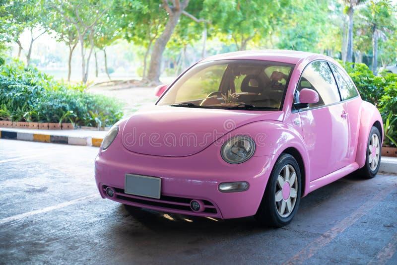 Автомобиль современной потехи розовый небольшой Фото современного в стиле фанк розового автомобиля припаркованного близко к хижин стоковая фотография