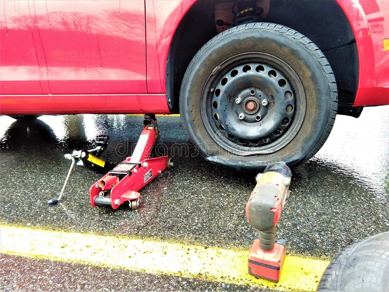 Автомобиль со спущенной шиной и инструментами стоковое фото