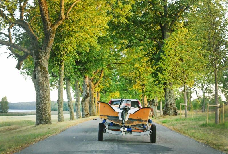 Автомобиль с моторной лодкой на трейлере на дороге стоковое изображение