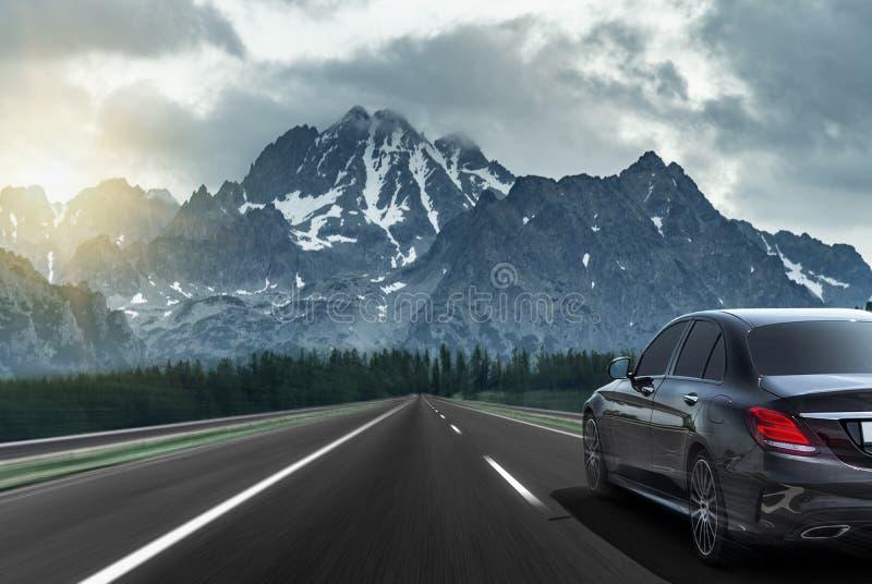 Автомобиль управляет быстро на шоссе против фона горной цепи стоковое изображение rf