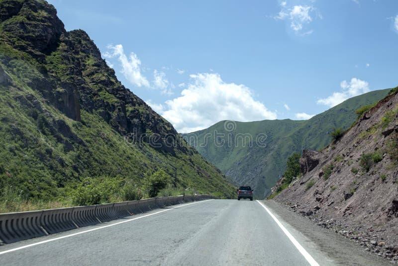 Автомобиль управляет вдоль дороги между живописными зелеными холмами Перемещение в Кыргызстане стоковые изображения rf