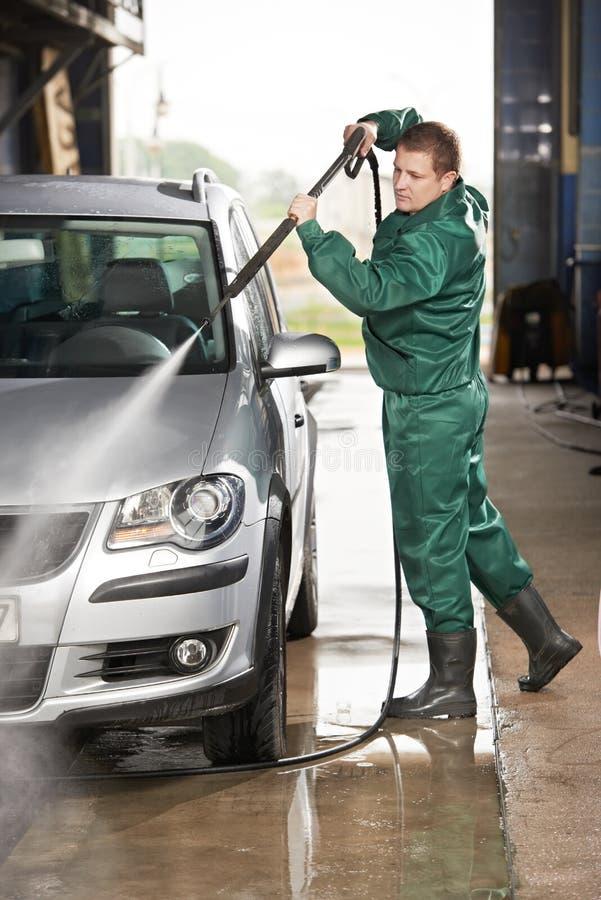 Автомобиль чистки работника с надавленной водой стоковое фото
