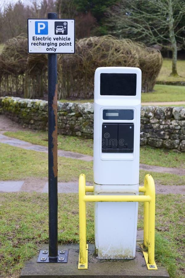 Автомобиль электротранспорта перезаряжая знак и зарядную станцию пункта заткнуть внутри парковку в парке стоковые фотографии rf