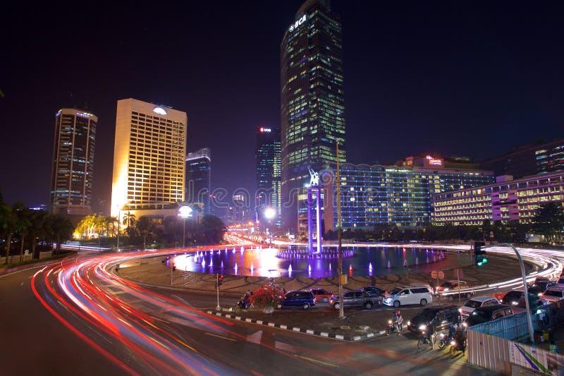 Автомобили и шины спешат через карусель Индонезии площади в финансовом районе Джакарты стоковые изображения