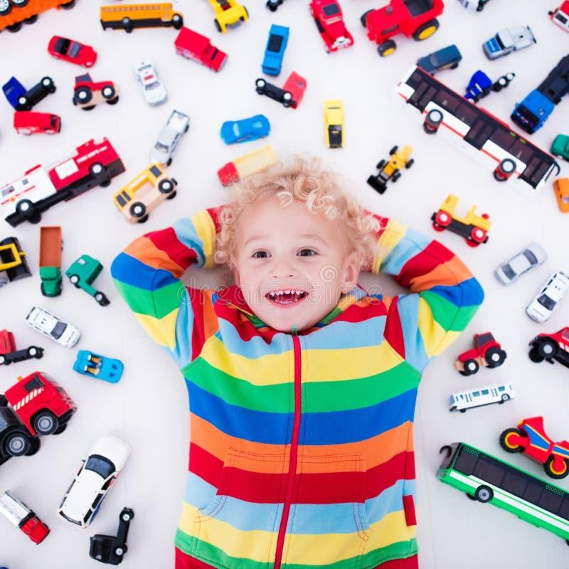 автомобили мальчика меньшяя играя игрушка стоковые фото