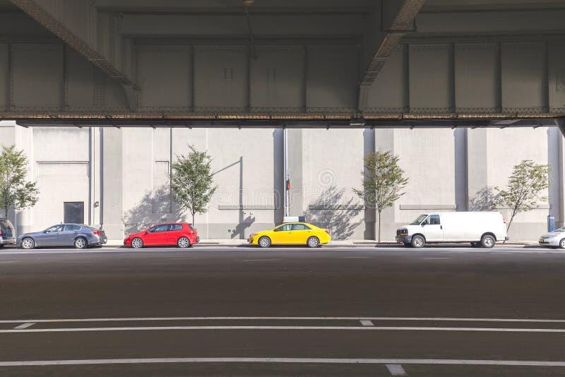 Автомобили припарковали на улице под мостом в Манхаттане стоковое изображение