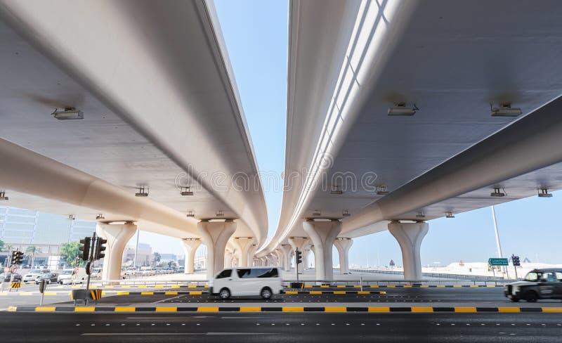Автомобили управляют на шоссе под автомобильными мостами стоковые фото
