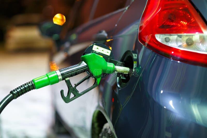 Автомобиль дозаправляя на бензозаправочной колонке в зиме на ноче стоковые фотографии rf