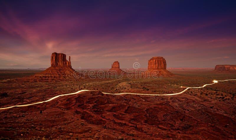 Автомобиль освещает следы в долине памятника на ноче стоковые фото