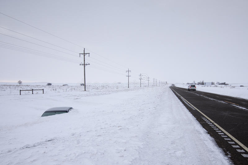 Автомобиль похороненный к своей крыше в глубоком снеге не далеко от дороги Северная Дакота, США стоковое изображение