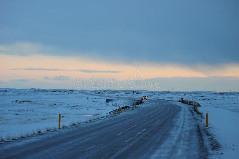 Автомобиль прошел мимо на кольцевую дорогу в зиме Исландии стоковая фотография
