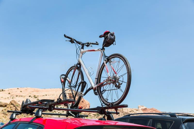 Автомобиль транспортирует велосипед на крыше стоковое фото