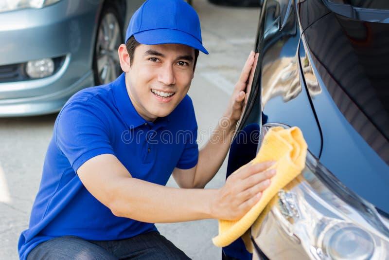 Автомобиль чистки молодого человека полируя с тканью microfiber стоковое фото