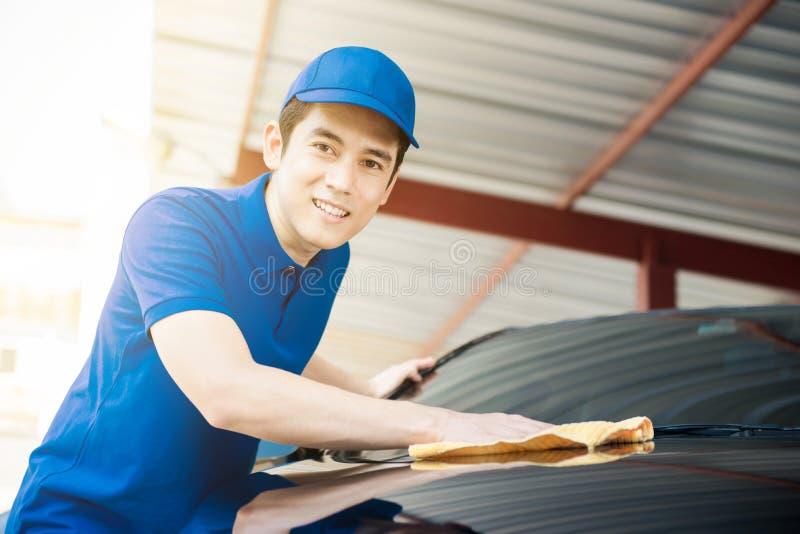 Автомобиль чистки человека полируя в гараже стоковые изображения