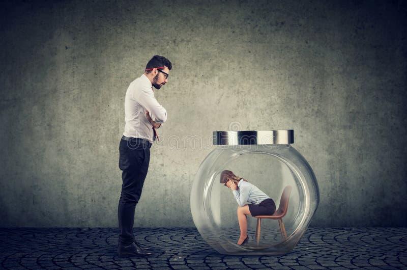 Авторитарный бизнесмен босса смотря стеклянный опарник с захваченной внутренностью женщины стоковая фотография rf