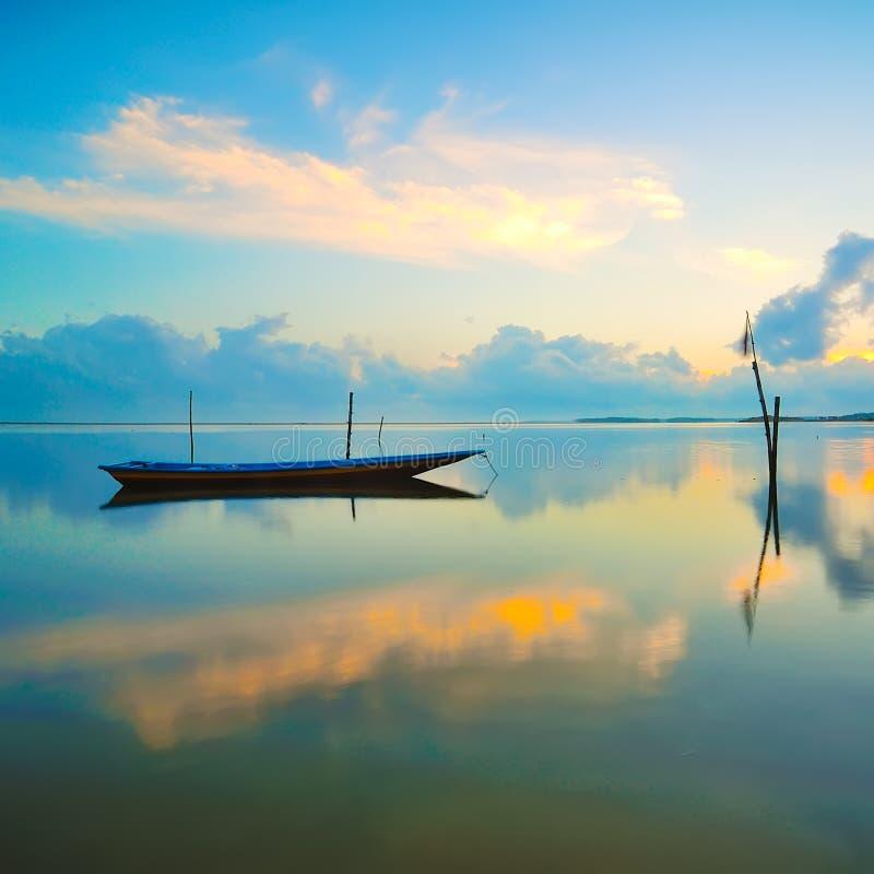 Автостоянка шлюпки рыболова с полным отражением во время восхода солнца стоковое фото rf
