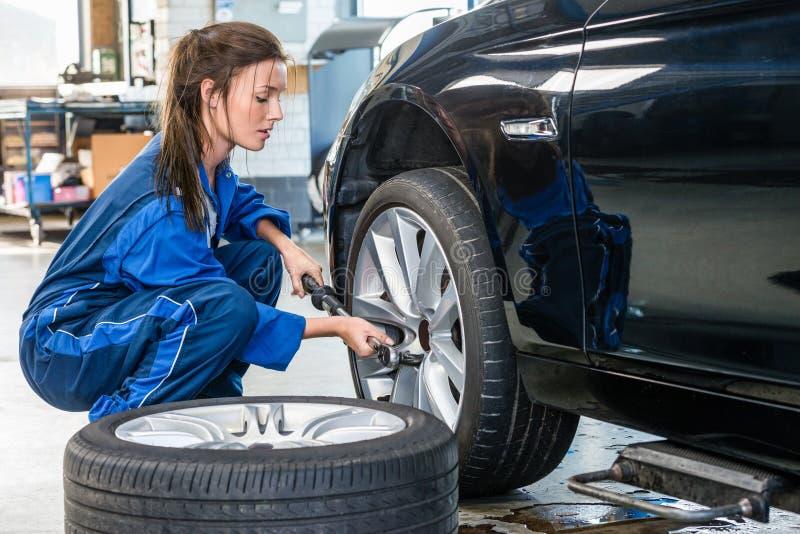 Автошина автомобиля женского механика изменяя на магазине автомобиля стоковое изображение