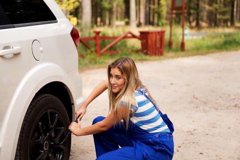 Автошина женского механика изменяя с ключем колеса стоковые фотографии rf