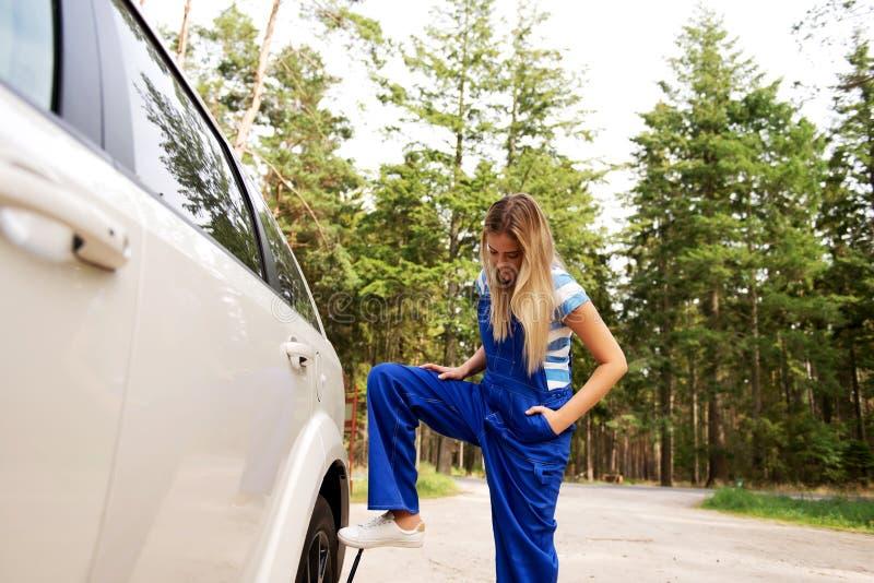Автошина женского механика изменяя с ключем колеса стоковая фотография