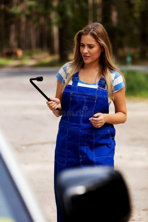 Автошина женского механика изменяя с ключем колеса стоковые изображения