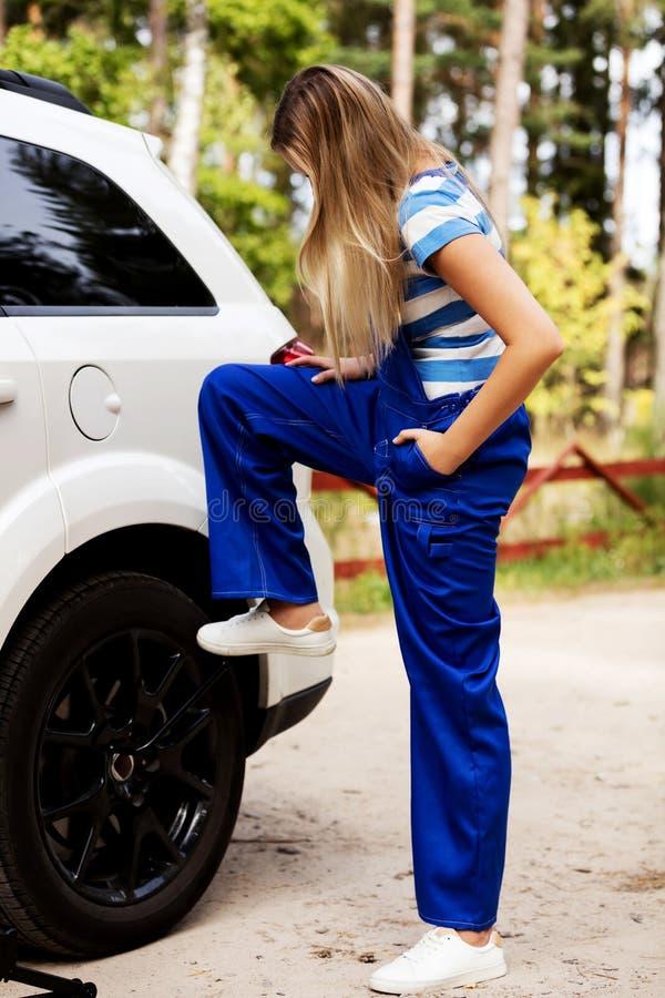 Автошина женского механика изменяя с ключем колеса стоковое изображение