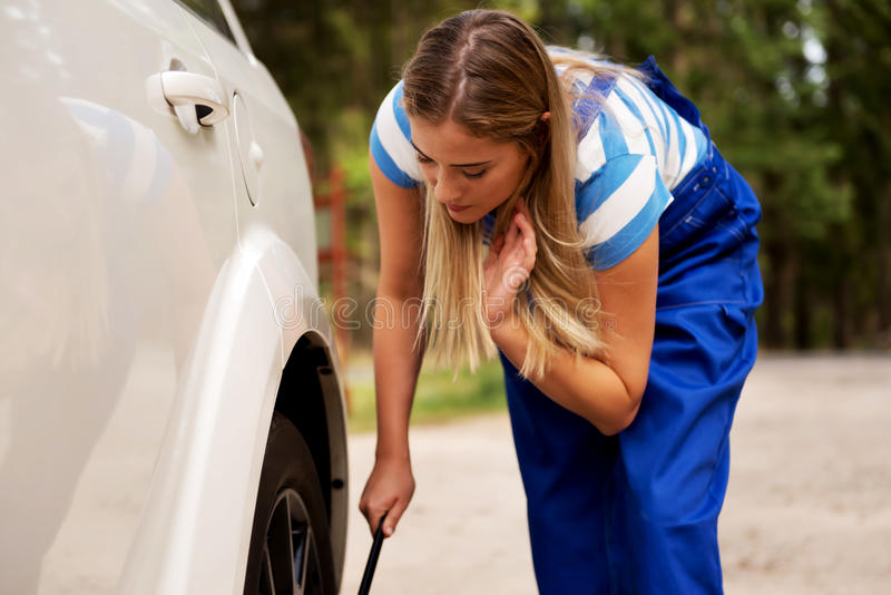 Автошина женского механика изменяя с ключем колеса стоковое изображение rf