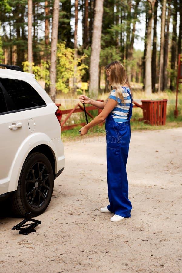 Автошина женского механика изменяя с ключем колеса стоковые изображения rf